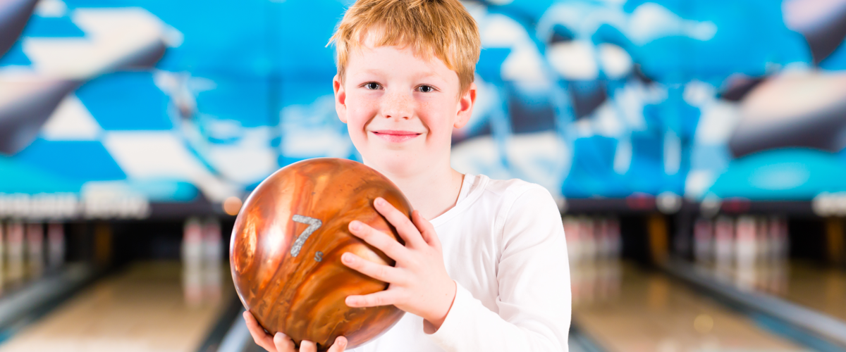 Child holding a bowling ball in a stance